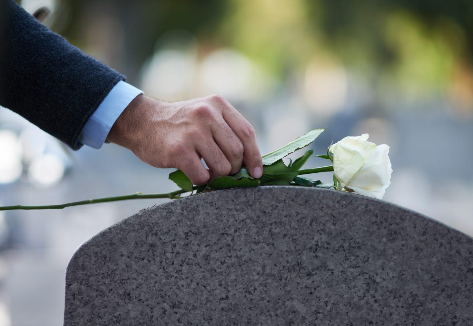 Mann legt Rose auf Grabstein