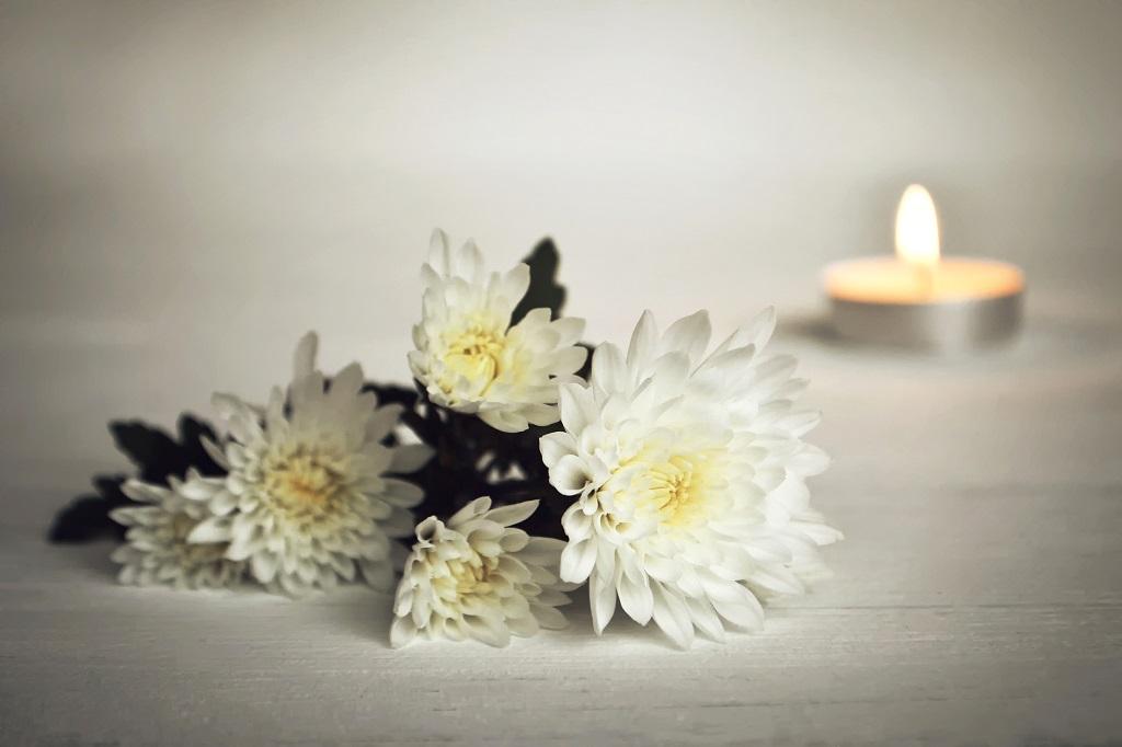 Kerze mit weißen Blumen